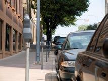 Geparkte Autos und Parkenmeßinstrumente stockbild