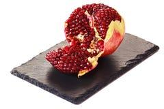 Gepeld granaatappelfruit op de zwarte plaat van de leisteen Rode sappige zaden binnen royalty-vrije stock foto's