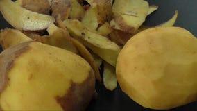 Gepelde aardappels en aardappelschil op de zwarte achtergrond stock videobeelden