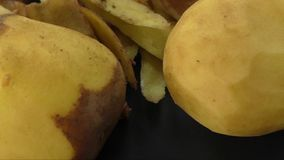 Gepelde aardappels en aardappelschil op de zwarte achtergrond stock footage