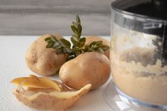 Gepelde die aardappels in een mixer op een witte achtergrond worden gemengd royalty-vrije stock fotografie