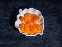 Gepelde die mandarin, in plakken in een decoratieve plaat wordt verdeeld stock fotografie