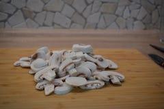 Gepelde en gesneden die paddestoelen, op een maaltijd van gebraden kippenborst worden voorbereid met paddestoelen en salade royalty-vrije stock afbeelding