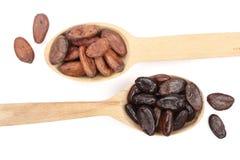 Gepelde en unpeeled cacaobonen in een houten die lepel op witte achtergrondclose-up hoogste mening wordt geïsoleerd Royalty-vrije Stock Foto