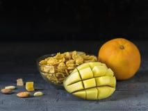Gepelde mango, sinaasappel, vlokken, en noten op een donkere houten lijst Stock Foto's