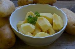 Gepelde potatos met peterselie in witte kom op houten achtergrond Royalty-vrije Stock Foto