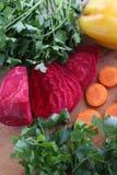 Gepelde rode bieten en verse wortelen voor salade op een houten lijst Stock Afbeelding
