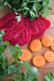 Gepelde rode bieten en verse wortelen voor salade op een houten lijst Royalty-vrije Stock Foto