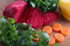 Gepelde rode bieten en verse wortelen voor salade op een houten lijst Royalty-vrije Stock Afbeeldingen