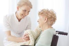 Gepensioneerde op rolstoelzieken op osteoporose stock foto