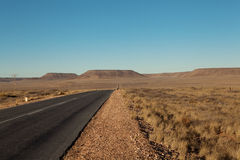 Gepflasterte Straße in der Wüste Lizenzfreies Stockbild