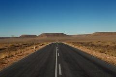 Gepflasterte Straße in der Wüste Lizenzfreie Stockbilder