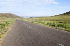 Gepflasterte Straße durch mongolische Steppen Stockfoto