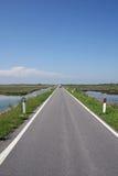 Gepflasterte Straße zwischen Meer zwei zur Unbegrenztheit und jenseits Stockfotos