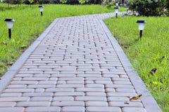 Gepflasterter Gartenweg mit Laternen mit Solarbatterien Stockbild