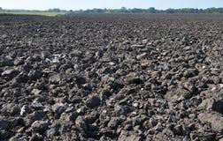 Gepflogen mit Traktorpflugfeld, nachdem Ernte aufgehoben worden ist lizenzfreies stockbild