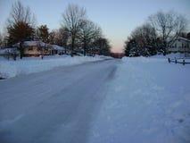 Gepflogene Straße im schneebedeckten Vorort Stockfotos