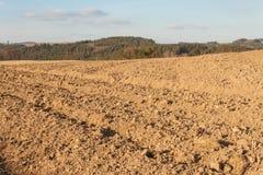 Gepflogenes Feld in der Landschaft in der Tschechischen Republik Der Frühling funktioniert auf dem Gebiet Ackerland Stockfotografie