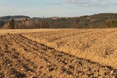 Gepflogenes Feld in der Landschaft in der Tschechischen Republik Der Frühling funktioniert auf dem Gebiet Ackerland Lizenzfreies Stockbild