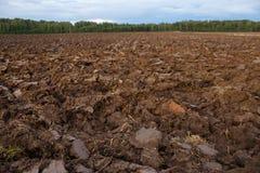 Gepflogenes Feld mit Traktor vollzieht im Frühjahr Zeit, Bauernhofbodenhintergrund nach Lizenzfreie Stockfotografie