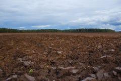 Gepflogenes Feld mit Traktor vollzieht im Frühjahr Zeit, Bauernhofbodenhintergrund nach Stockfoto