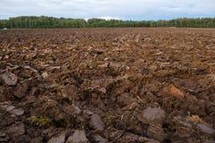 Gepflogenes Feld mit Traktor vollzieht im Frühjahr Zeit, Bauernhofbodenhintergrund nach Lizenzfreies Stockfoto