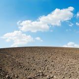 Gepflogenes Feld und blauer Himmel mit Wolken Lizenzfreies Stockfoto