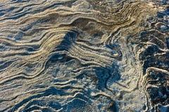 Geplätscherter Felsen neben dem Seehintergrund stockbild
