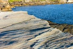 Geplätscherter Felsen neben klarem blauem Meer stockfoto