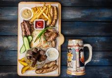 Geplaatste biersnacks Geroosterde die worsten en frieten met tomaat en BBQ saus, op scherpe raad met de antiquiteit wordt gediend royalty-vrije stock foto