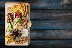 Geplaatste biersnacks Geroosterde die worsten en frieten met tomaat en BBQ saus, op scherpe raad wordt gediend royalty-vrije stock fotografie