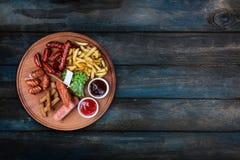 Geplaatste biersnacks Geroosterde die worsten en frieten met tomaat en BBQ saus worden gediend royalty-vrije stock afbeeldingen