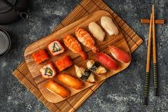 Geplaatste sushi: sushi en sushibroodjes op houten plaat Stock Fotografie