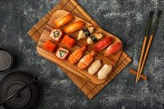 Geplaatste sushi: sushi en sushibroodjes op houten plaat Stock Foto