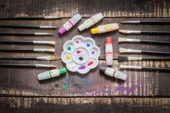Geplaatste verfborstels en een palet met olieverfbuizen Stock Foto