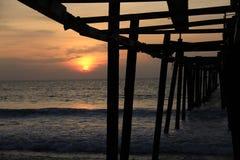 Geplaatste zon en de oude houten brug Stock Foto