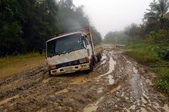 Geplakte vrachtwagen bij modderige weg Royalty-vrije Stock Fotografie