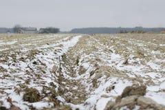 Geploegd land in de winter met diepe voren die met sneeuw worden bestrooid stock fotografie