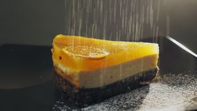 Gepoederde suikerdalingen bovenop een cake en een plaat in langzame motie stock video