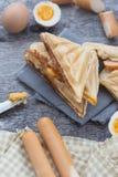 Gepresstes und geröstetes doppeltes panini mit dem Schinken und Käse gedient auf Sandwichpapier auf einem Holztisch, Ei, Würstche stockbild