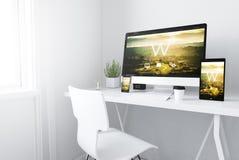 Geräte auf entgegenkommender Designwebsite des weißen minimalen Arbeitsplatzes lizenzfreies stockbild