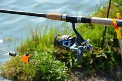 Geräte für die Fischerei: Stange mit einer Spule Fischerei auf der Flussbank Lizenzfreie Stockfotos