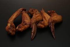 Geräucherte Hühnerflügel auf einem schwarzen Hintergrund mit Kopienraum für Text lizenzfreies stockbild