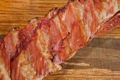 Geräucherte Schweinefleischrippen saftig und fleischig auf einem hölzernen Schneidebrett lizenzfreie stockfotos