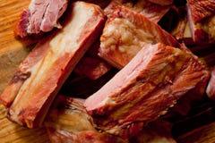 Geräucherte Schweinefleischrippen saftig und fleischig auf einem hölzernen Schneidebrett lizenzfreie stockbilder