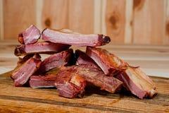 Geräucherte Schweinefleischrippen saftig und fleischig auf einem hölzernen Schneidebrett lizenzfreies stockbild