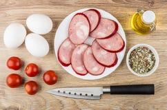 Geräucherte Wurst in der Platte, Tomaten, Eier, Gewürze, Pflanzenöl Lizenzfreie Stockfotografie
