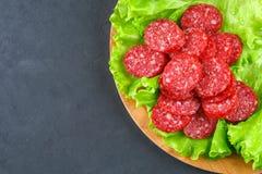 Geräucherte Wurst, Salami hackte in den Scheiben auf einem Salat auf einem hölzernen Kreisschneidebrett auf einer konkreten graue Lizenzfreie Stockfotografie