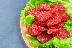 Geräucherte Wurst, Salami hackte in den Scheiben auf einem Salat auf einem hölzernen Kreisschneidebrett auf einer konkreten graue Lizenzfreie Stockfotos