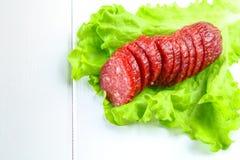 Geräucherte Wurst, Salami hackte in den Scheiben auf einem Salat auf einem hölzernen Kreisschneidebrett auf einer weißen Tabelle Lizenzfreies Stockbild